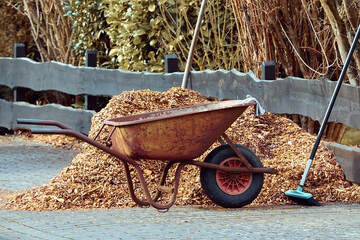 A wheelbarrow and mulch used for flower beds to retain moisture and help eliminate weeds.