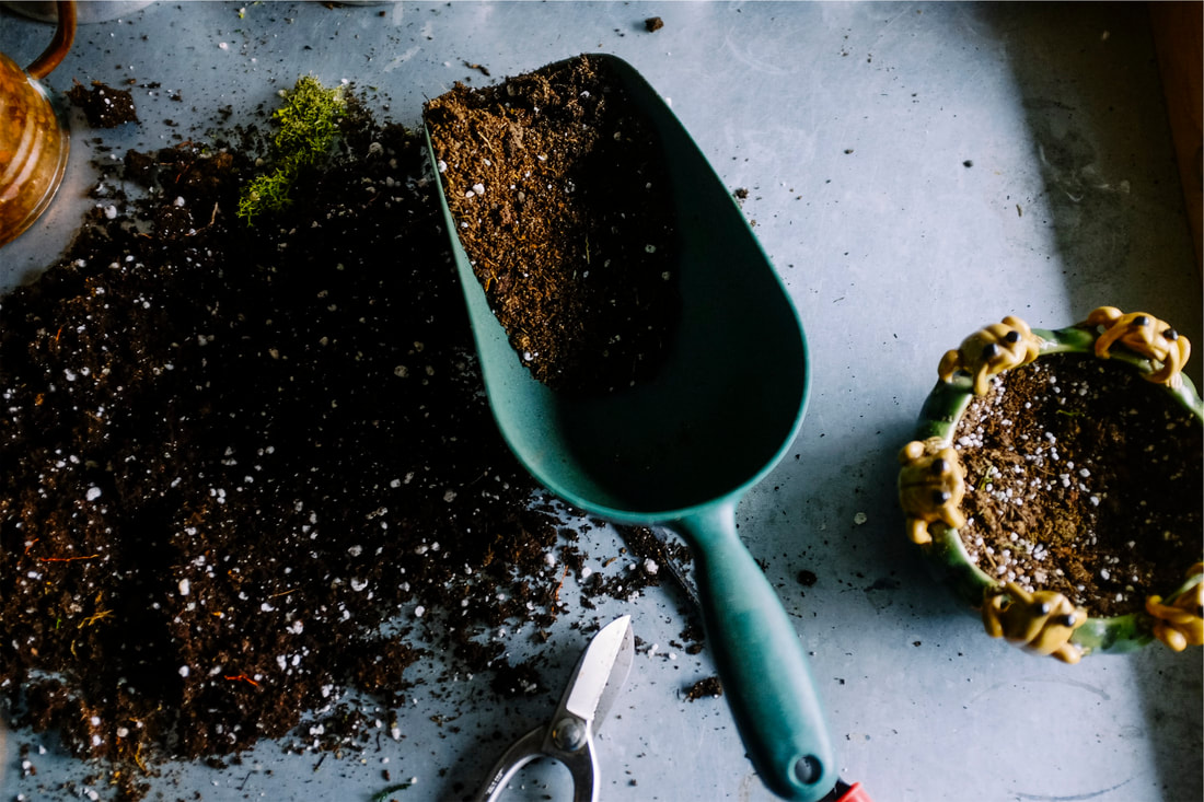 A trowel and topsoil helpful in planting and relocating flowers.
